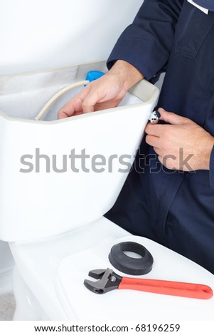 Plumber repairing a flush toilet - stock photo