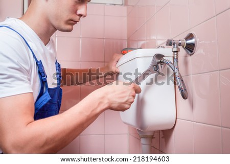 Plumber repairing a toilet pipe with a wrench - stock photo