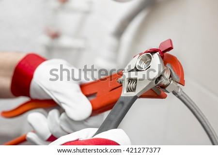 plumber screwing plumbing fittings in bathroom - stock photo