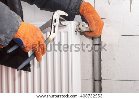 plumber to connect the heating radiator to a polypropylene pipe - stock photo