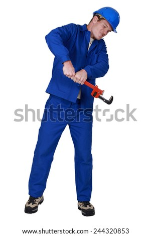 Plumber using a pipe wrench - stock photo