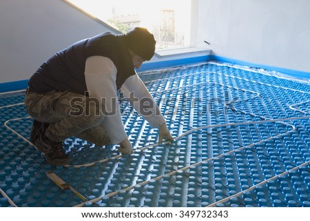 Plumber working installed system radiant floor - stock photo