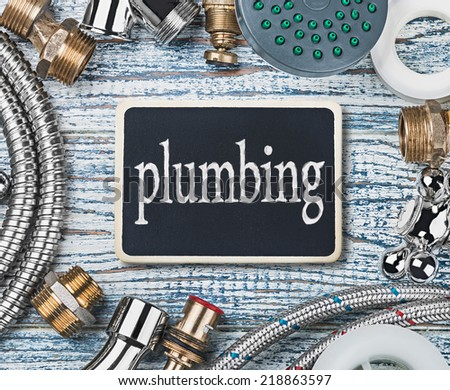 plumbing and accessories on wooden table background - stock photo