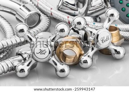 plumbing and tools in a light background. Focus on plumbing taps - stock photo