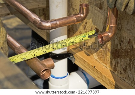 Plumbing contractor works on the copper pipe domestic water system on a luxury custom home - stock photo