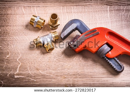 Plumbing Tools Composition Of Brass Pipe Connectors On Wooden Board and Monkey Wrench  - stock photo