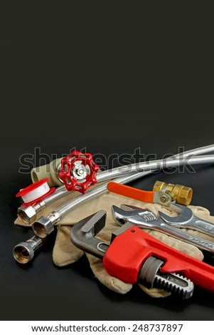 Plumbing tools on black background. - stock photo
