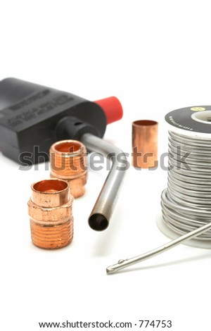 Plumbing torch, solder, and some copper pipe fittings - stock photo