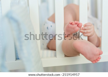 plump legs and handle the baby to hold on to the bars of baby white cot, close up - stock photo