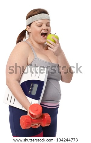 Plump woman biting green apple, holding dumbbells and scale in sportswear. - stock photo