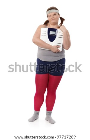 Plump woman in sportswear holding a scale in hands, looking away. - stock photo