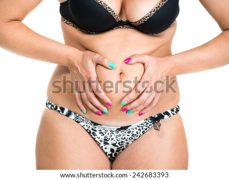 Plump woman pinching her fat tummy on a white background - stock photo