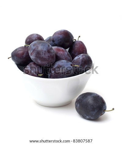 plums in white bowl over white - stock photo