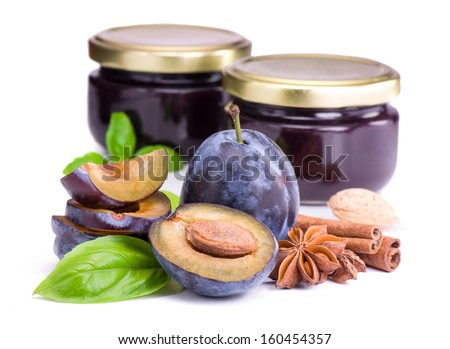 Plums with  basil leaves,anise and jam in glass jars - stock photo