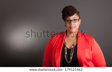 Plus size black woman wearing glasses in a smart business outfit on a neutral grey background - stock photo