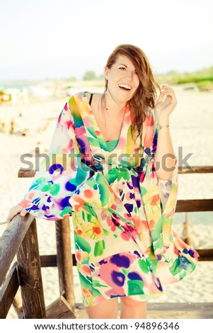 Plus size model is standing on a beach tower and smiling. - stock photo
