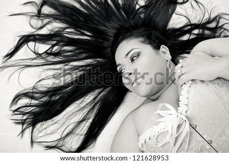 Plus size model posing like fashion models. The woman is posing is on the floor with her hair like Medusa, in a sexy manner. - stock photo