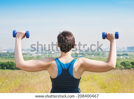 Plus size woman exercising with dumbbells - stock photo