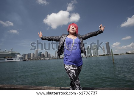 Plus size woman posing by the bay with arms outstretched - stock photo