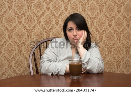 Plus size woman with a cup of coffee in a bathrobe - stock photo