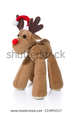 Plush reindeer with Santa hat isolated with a red christmas hat - stock photo