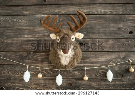 Plush toy deer on a wooden wall with xmas balls - stock photo