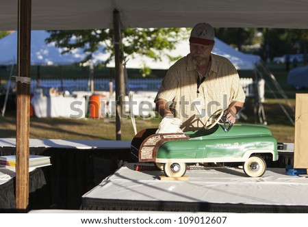 PLYMOUTH - JULY 29 : A A vendor prepares an antique pedal car to go on display at the Concours D'Elegance  July 29, 2012 in Plymouth, Michigan. - stock photo