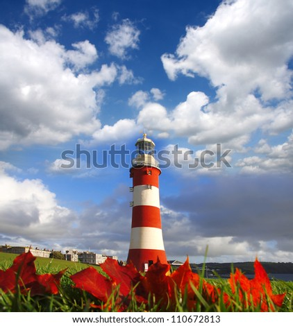 Plymouth Lighthouse with autumn leaves in England - stock photo