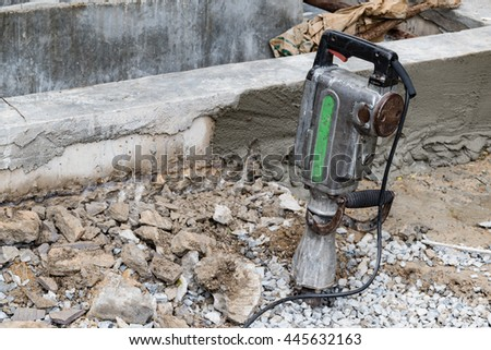 pneumatic hammer drill equipment for breaking Concrete at road construction site,Shallow depth of field,selective focus on hammer drill ,left space for text  - stock photo