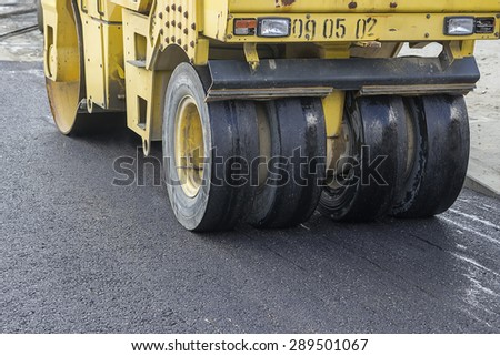 Pneumatic tyred roller compacting asphalt. Street paving works. Selective focus and shallow dof. - stock photo