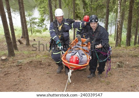 Pnovany, Czech Republic, June 4, 2014: Training rescue injured people in difficult terrain at the dam Hracholusky, carrying a stretcher with an injured person - stock photo