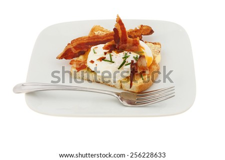 Poached egg on toast with pancetta and chives on a plate with a fork isolated against white - stock photo