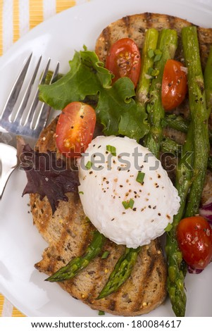 Poached egg on toasted bread with asparagus, tomatoes, greens  - stock photo