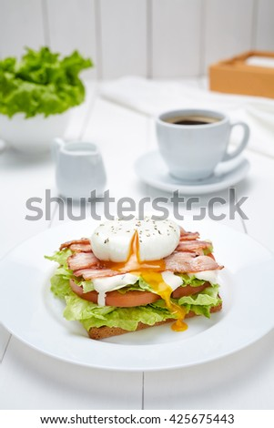 Poached egg sandwich with bacon, salad, mayonnaise, tomatoes, toasted bread and a cup of coffee. Concept of morning breakfast. Restaurant menu meal - stock photo
