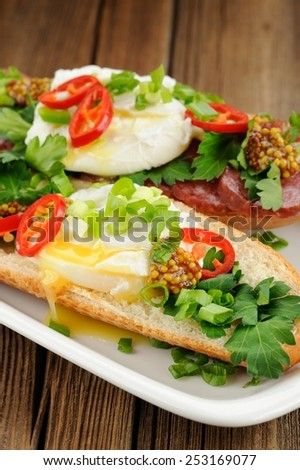 Poached egg sandwiches with chili, scallion and salami - stock photo