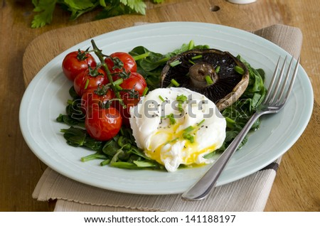Poached egg with spinach, Portobello mushrooms and vine tomatoes - stock photo