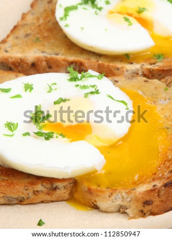 Poached eggs on buttered wholemeal toast breakfast. - stock photo