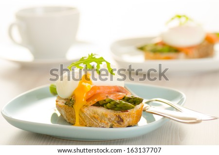 Poached eggs with salmon and asparagus on toasted bread  - stock photo