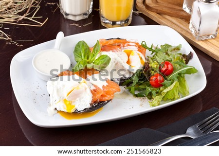 Poached eggs with salmon on toasted bread - stock photo