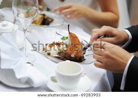 Poached pear with an ice cream in red wine sauce - stock photo