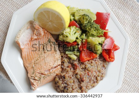 Poached wild salmon with dill herb, tricolor quinoa, lentil and vegetables recipe with green broccoli florets and red sweet bell pepper with a lemon half - stock photo