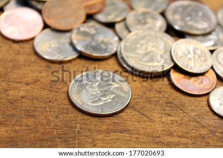 Pocket change, various coins over on old wood surface - stock photo
