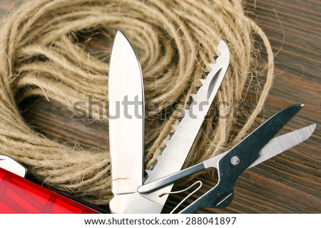 Pocket knife with rope on wooden table close up - stock photo
