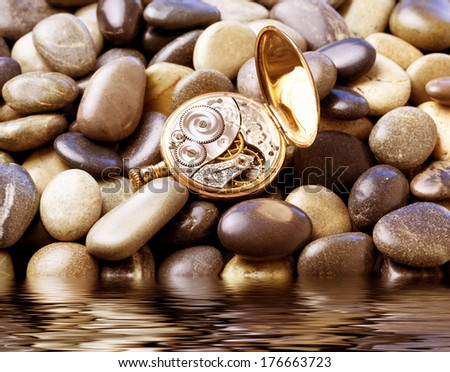 Pocket watch laying over stones by the water - stock photo