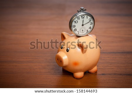 Pocket watch on a piggy bank on a brown table - stock photo