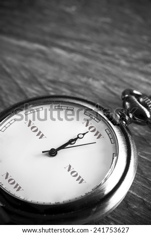 "pocket watch on a vintage table showing the time ""now"" - stock photo"
