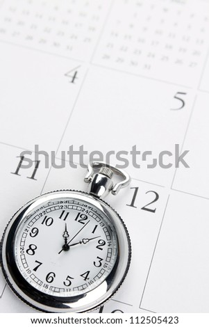 Pocket watch on calendar page - stock photo