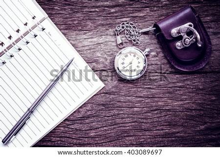 Pocket watch on notebook for notes, On old textured wood. Vintage style. - stock photo