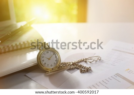 Pocket watch on work table at morning time,selective and soft focus. - stock photo