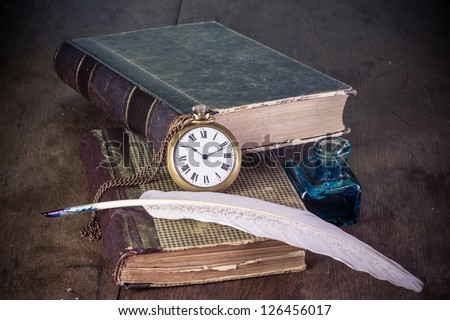 Pocket watch, quill pen and inkwell, book on the table - stock photo